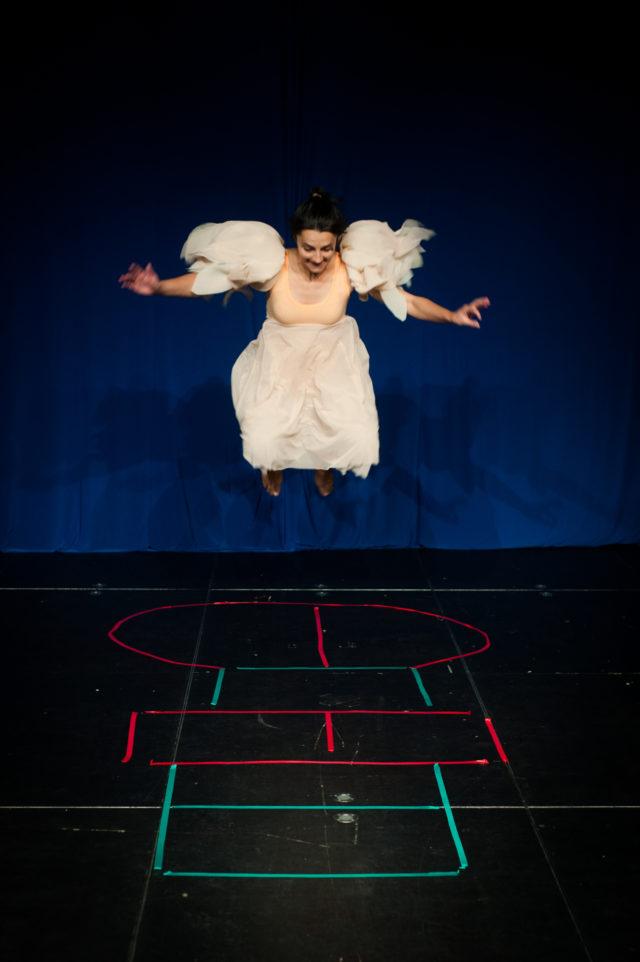 kobieta zer skrzydłami anioła skacze w grę w klasy